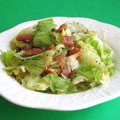 Grandma's Wilted Lettuce Salad: Cut up one head of lettuce.  Cut up 5 to 6 slices bacon into small pieces.  Fry brown.  Put bacon chips on lettuce.  Pour off some of the bacon grease if desired.  To bacon grease, add 1/4 cup vinegar, 1/2 cup sugar and 1/4 cup water.  Bring to boil.  Boil to thick and pour over lettuce.  Salt and pepper.