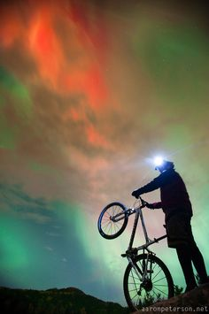 Night mountain bike riding with aurora borealis northern lights near Marquette Michigan. - Photo by: Aaron Peterson
