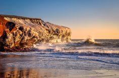 Les vagues qui viennent se briser sur les falaises gelées des Îles de la Madeleine : | 15 paysages d'hiver inoubliables que vous ne verrez qu'au Québec