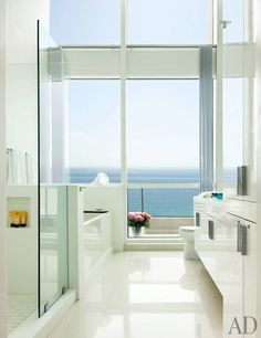 Designer John Barman understands the transformative power of even a small renovation. To take advantage of all the extraordinary ocean views at his apartment in Miami Beach, he ripped out the false ceiling in the bathroom and installed dramatic double-height windows | archdigest.com