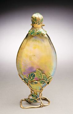 "Tiffany Studios scent bottle-on-stand, circa 1900. Inscribed mark ""Ex."" identifies the piece as one displayed at an international exhibition, such as a World's Fair or one of the annual Paris Salons. The rampant Art Nouveau exuberance of its foliate mount, uncharacteristic of Tiffany's standard style suggests that the piece was designed specifically for display in Paris."