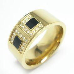 Anillo acero con baño PVD oro con aplicacion en negro y circones blancos. Medidas: 13-14 $19.000.-