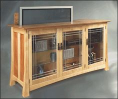 Flat-Screen TV Lift, leaded glass doors, shallow shelves in front of TV lift with full depth shelves on the end.