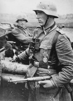 An Oberfeldwebel (Master Sergeant) of Panzergrenadier Division Grossdeutschland stands aside his field car. Inside the field car are his driver and his dog. The Oberfeldwebel here is armed with an MP-38, and has the General Assault Badge (Allgemeines Sturmabzeichen) for participating in combat while being in a non-infantry unit.