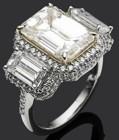 A diamond three-stone ring.   The yellow tinted step-cut diamond weighing 6.14 carats, flanked by a pair of baguette-cut diamonds weighing 1.20 and 1.03 carats each, to the micro-pavé diamond gallery and shoulders, mounted in platinum and 18 carat yellow gold. Bonhams.