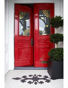 """Tradition Reinvented: A bold yet classic color—Benjamin Moore's Heritage Red, to be exact—in a high-gloss finish took this home's Victorian-era door from staid to stunning. The gilt stencil detail on the glass completes the look. Get more happy and cheerful interior design ideas on """"7 Fabulous Colorful Front Door Ideas"""" on the One Kings Lane Style Guide!"""