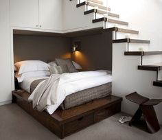 Bed Under Stairs - Instead of storing random junk under it, these designers put a queen sized bed in the cozy corner, complete with a reading light.