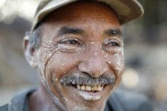 """Ramon and his """"R"""" tooth smile: An miner named Ramon flashes a gold letter """"R"""" on his tooth as he smiles after working in a mine in the southern state of Bolivar. In the triangle that connects Venezuela, Brazil, and Guyana, a large number of illegal gold and diamond prospectors dream of changing their lives overnight by finding a huge bonanza."""