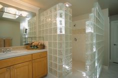 "Walk-in, door-less Glass Block Shower Walls constructed with 8""x8"" & Hedron block from Pittsburgh Corning in the Decora pattern. These prefabricated Glass Block panels were constructed in rows of 2 and installed in just a fraction of the time as traditional mortar built Glass Block Showers. Light from an exterior window is transmitted though the entire bathroom with use of Glass Blocks in this shower. Endblocks and Stylecap glass tiles were used to finish this Glass Block Shower."