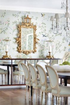 Chinoiserie - This classic gilt chinese chippendale mirror looks terrific featured on a light blue chinoiserie wallpaper.   The mirror is flanked by two overisized hurrricane lanterns, which are held up on a modern mirrored sideboard.  The antique Louis XV chairs complete this very elegant dining room.