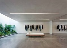 Standard Architecture has completed a new store for the fashion brand Helmut Lang that features smooth plaster walls, cove lighting and a garden