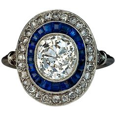 Art Deco Sapphire Diamond Engagement Ring. A platinum milgrain ring of an oval shape centered with a bezel set sparkling antique cushion cut diamond (7.3 x 6.8 x 4.85 mm, approximately 2 carats, K color, VS2 clarity) outlined by a row of tapered calibre cut deep blue sapphires and further set with a border of old rose cut diamonds c 1915