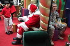 U.S. Army Sgt. Benjamin Thwing of Cleveland waits in hiding behind the grand chair of Santa Claus, portrayed by Bob McClain, as Thwing's son Jordyn, 5, approaches to make the wish to be with his father for Christmas.