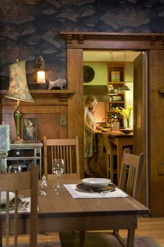 In the dining room, quarter-sawn oak woodwork was never altered; Michelle works at the kitchen's center island beyond