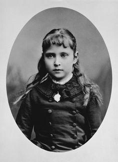Princesa Alix de Hesse; seu longo cabelo cai sobre os ombros. Ela usa vestido de mangas compridas com babado no pescoço. Fevereiro de 1879.