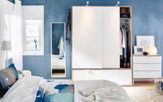 Chambre avec une grande armoire blanche à deux portes coulissantes et quatre tiroirs,  ainsi qu'une commode blanche 3 tiroirs et un miroir.