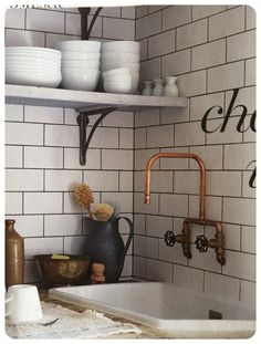 Copper pipe tap and vintage styling against white metro / subway tiles