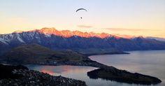Entardecer em Queenstown. Ao fundo a cadeia de montanhas The Remarkables, o lago Wakatipu e a cidade abaixo. No ar, praticante de paragliding sobrevoa a cidade. Esse panorama pode ser visto do alto do teleférico Skyline, em Queenstown