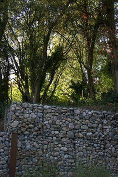 Gabion walls..........a wonderful way to create a sturdy backyard fence by the creek