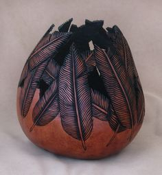 When falcons soar through Arizona canyon country, occasionally a feather drops to earth. This kettle gourd bowl captures a dozen of them in intricate 3-dimensional detail through pyrography and careful carving and cutwork. A wash of wood dyes give the rich red mahogany tone, and ebony shades the tiniest delicate flutings of each feather. Feathers in dreams signify travel and a fresh start.