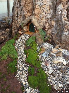 Green Fairy Door with portico made from woven willow, covered with moss.