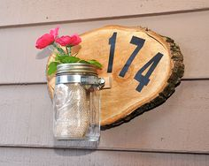 Attach vinyl numbers to create a new house sign, adding a Mason jar filled with delicate flowers for a charming touch. What a welcoming way to welcome guests into your home.