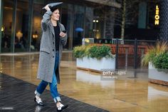 Jo Ellison, FT fashion editor, wears a patterned gray coat, jeans, and black and white loafers and shields herself from the rain with a black leather portfolio during London Fashion Week Autumn/Winter 2016/17 at the Anya Hindmarch show at Kings Cross on February 20, 2016 in London, England.