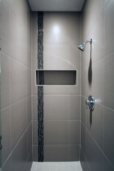 The porcelain tile of this sleek shower surrounds a glass accent tile stripe and built-in niche to store shower accessories. The dark shades of the glass tile add a contrast to the light neutral walls and white floor. A stainless steel shower head and handle are mounted into the wall.