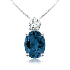 A glimmering London blue topaz is topped with a precious round diamond, both held in a prong setting. The greenish blue brilliance of the oval gemstone is augmented by the diamond accent. This simple yet elegant 14k white gold London blue topaz solitaire pendant has intricate scroll detailing on the sides.