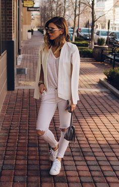 Street style look com calça branca rasgada, blazer e tênis.