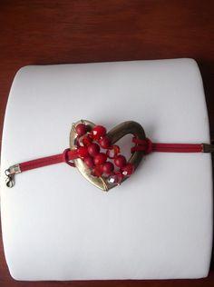Pulsera con dije de corazon bordada con cuentas rojas..