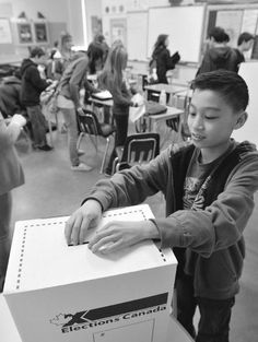 Grade 7 pupil Jack Yeung casts his ballot in a mock vote for students at Spruce Avenue junior high school. (AB)