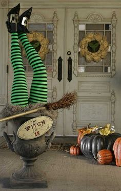Upside down halloween witch decor. Witch legs in pot with a decorative broom and funny sign. I'm in love with this decor!