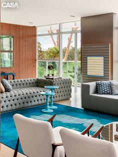 As salas de estar e jantar destacam tons de azul e verde. Junto ao tapete…