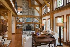 A dual-sided stone hearth connects the great room and master bedroom suite in this Virginia timber home. The intricate beam work pairs perfe...