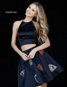 This Sherri Hill 51397 two-piece short dress pairs a sleek halter neck top with a semi-open back and an A-line skirt adorned with multi-colored beaded hearts. The box pleated skirt has an above the knee hemline.