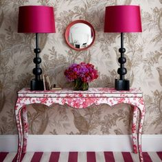 The pink floral console has an edge with its nail head trim, and sets the tone for the other choices in the vignette. Pink is repeated with dramatic style on the shades, flowers and striped rug.