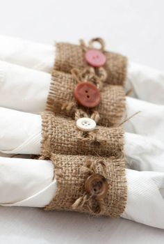 Lot of 50 handmade burlap napkin rings with button and twine bows. Buttons come in a variety of muted, earthy colors. Perfect for a rustic country wedding.    Each napkin ring measures about 2 tall and 4.5 around.    Ships out within 1 to 3 days of purchase via USPS with delivery confirmation from Austin, TX.