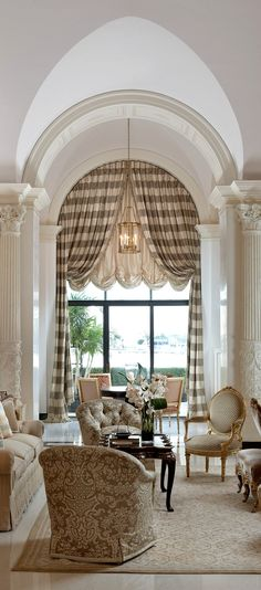 A layered drapery and valance is a fool proof and moderately priced way to treat an arched window. Notice the plaid is straight. The drapery must either fall behind the arch or be perfectly cut in the radius of the arch to achieve straight lines within the drapery. comment: DesignNashville