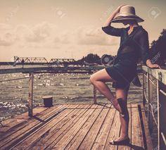 Donna alla moda in bianco cappello in piedi su vecchio di legno Molo Foto, Immagine e esente da diritto. Immagine 20.569.730.