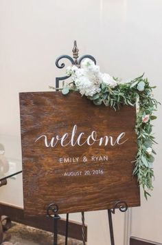 Piazza on the Green wedding sign draped with floral greenery. Pink and white flowers. McKinney Texas wedding venue. Wedding decor ideas.
