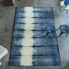 Savine Indigo Rug A spectacular hand woven pure wool rug, authentically tie dyed making each unique and distinctive. The natural ombres shade from bright daylight tones to deep rich indigo.