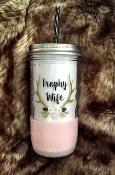 Adorable cup for a Trophy Wife or Future Trophy Wife ♥  Customize all colors and add a name to the back if you would like! ♥ Overview ♥ 24 oz Mason Jar with reusable acrylic straw in a complimentary/matching color ♥ Also available as a 32 oz water bottle, 16 oz Latte Mug or 11oz To Go Coffee Tumbler ♥ Available with or without glitter ♥ Design is applied with high quality, permanent vinyl rated for outdoor use ♥ Glitter is sealed to prevent shedding *Please note that the mason jar is clear…