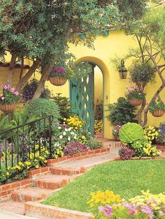 Frame a Gate - A bright yellow house is a perfect foil for a colorful mix of blooms in a front yard garden. The bright stucco wall, brick walkway, and colorful blooms combine beautifully to enhance a Spanish theme in this front yard. Porches, Brick Walkway, Front Walkway, Stucco Walls, Yellow Houses, Exterior, Front Yard Landscaping, Landscaping Ideas, Courtyard Landscaping