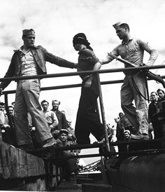 Marines unloading Japanese POW from a submarine returned from war patrol. Ca. May 1945. Lt. Comdr. Horace Bristol. (Navy)