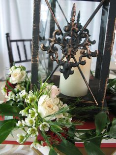 Lantern with greenery ring and spray roses.
