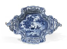 A rare Dutch Delft blue and white basket, circa 1758-65 of oval quatrefoil form with two high scrollwork handles, intricately pierced on the sides, reserving a painted cartouche of a wandering duck in a pond, A/D/12 in blue for Jan Teunis Dextra of De Grieksche A (The Greek A) factory, blue 115, incised letter F, 33.3cm., 13 1/8 in. across handles