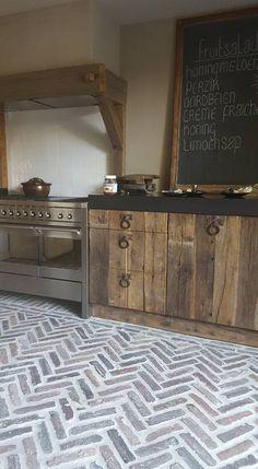 A rustic kitchen with chevron pattern brick flooring.