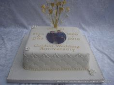 Square 50th Golden wedding anniversary cake covered in an ivory icing topped with a photograph and finished with pearlecent bead ribbon ivory and gold coloured feathers and hearts shimmered in an explosive topper