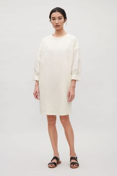 This dress is made from a cotton jersey with a contrasting cotton poplin sleeves and shoulder details. A straight fit, it has dropped shoulders, subtle in-seam pockets and double topstitch finishes.